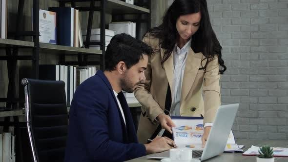 Geschäftsmann und Frau suchen Papierkram