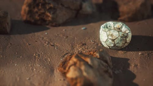 Old Football Ball on the Sand Beach