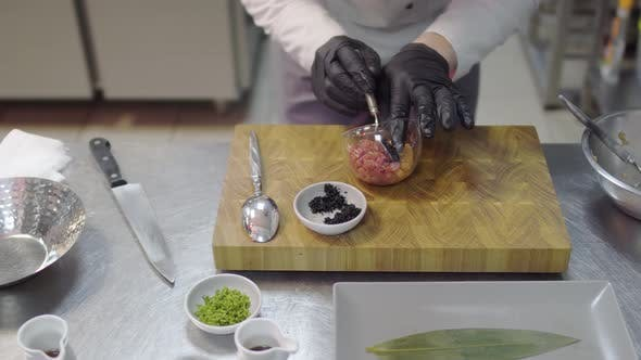 Thumbnail for Chef in Black Rubber Gloves Preparing Dish with Raw Tuna and Salmon in Modern Restaurant Kitchen