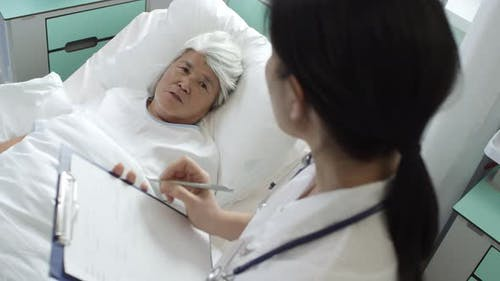 Female Doctor Supporting Recovering Senior Lady