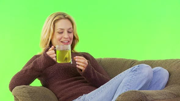 Thumbnail for Woman steeping and drinking tea on her couch