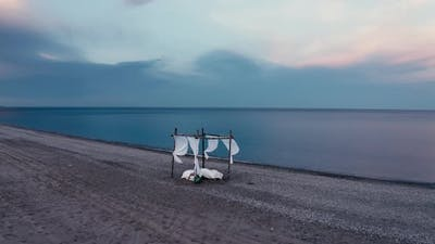 Four poster bed by the sea on the beach