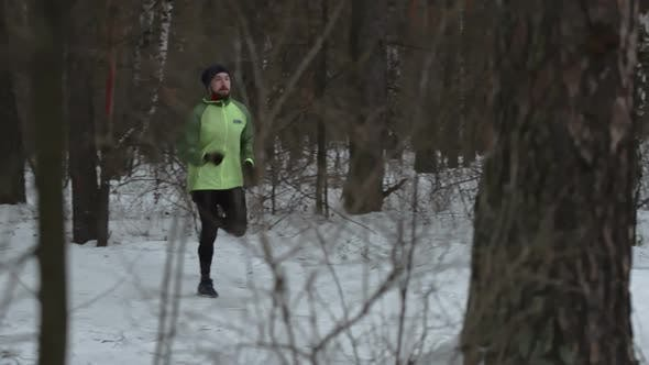 Thumbnail for Young Man Athlete Running Through Winter Forest