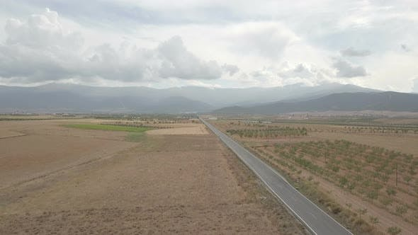 Thumbnail for 4K Aerial View Of Straight Tarred Road Through Guadix, Granada. In the background Sierra Nevada