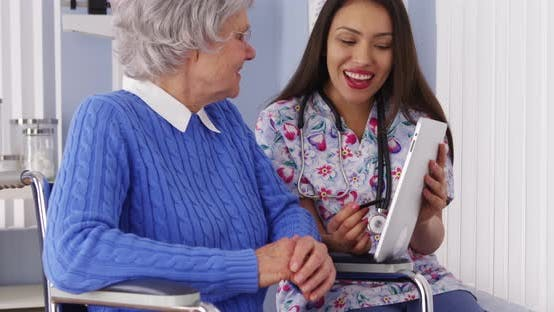 Thumbnail for Friendly Mexican caregiver talking to elderly patient with tablet