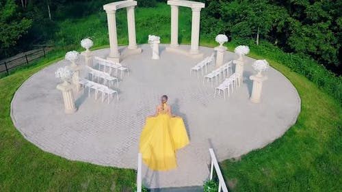 Aerial Shot of Young Charming Girl, in Beautiful Yellow Evening Dress, Lit Up By Sun, Rises Up Hill