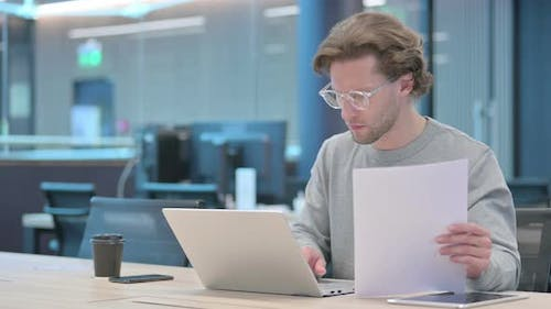 Businessman with Laptop Reading Documents in Office