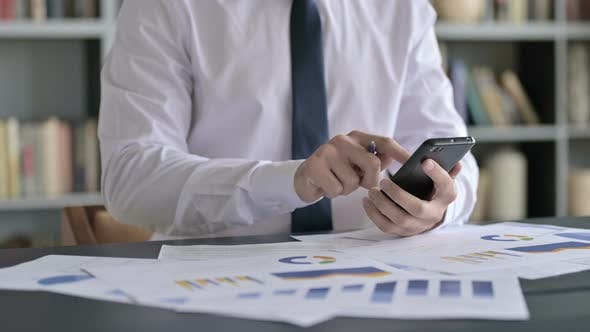 Thumbnail for Close Up Shoot of Businessman Working on Documents with Cellphone