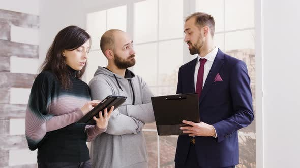 Thumbnail for Real Estate Agent Talking with Couple and Holding Documents