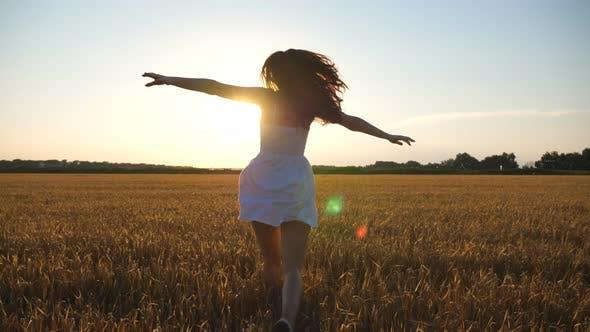 Thumbnail for Attraktive fröhliche Frau in weißem Kleid läuft durch Feld von Weizen bei Sonnenuntergang