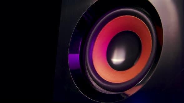Macro Close Up of Black Vibrating Membranes Loud Sound Speaker in Colorful Neon Lighting