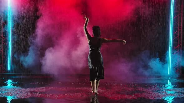 A Passionate Performance of Spanish Flamenco Dance in the Rain. A Charming Young Woman Dances on the