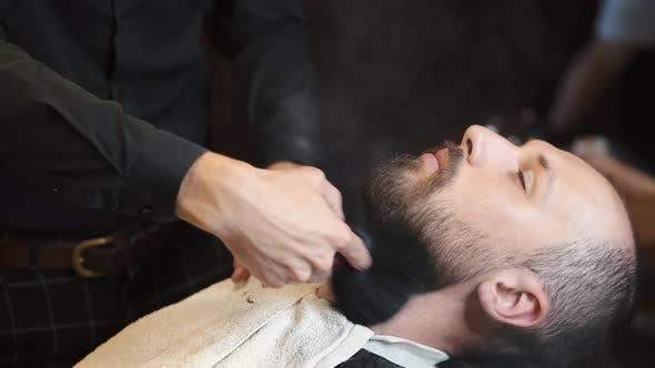 Barber Applying Lotion on Mans Beard