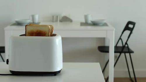 Fried toast jump out from a toaster in a kitchen