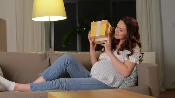 Curious Pregnant Woman with Gift Box at Home
