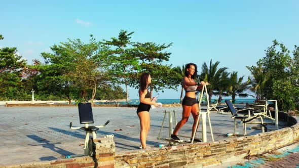 Thumbnail for Young Smiling Girls on Photoshoot in The Sun at The Beach on Paradise White Sand and Blue
