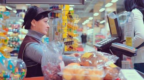 Woman at the Cash Desk Putting Merchandise on Conveyor Belt