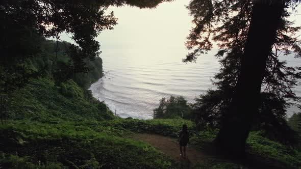 Thumbnail for Girl Traveler Goes Down To Cliff Hill in Mountain Forest, Sea Bay and Waves. Tropical Plants, Trees