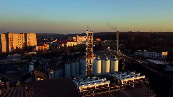 Aerial view of a drone flying over the beer production plant, several rows of tanks.