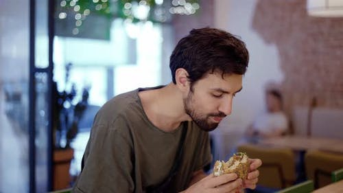 Unshaven c Man Eats Meat Burger with Pleasure Bites Burger with His Mouth