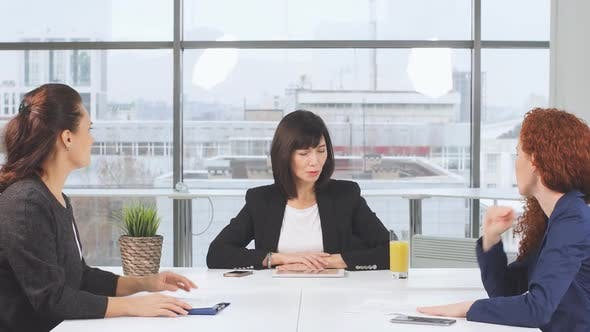 Thumbnail for Determined Business Partners Actively Studying Business Documents at Wooden Conference Table