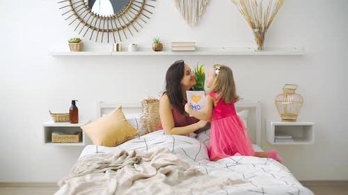 Kleines Mädchen gratuliert Mutter am Morgen