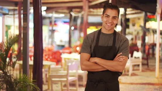 Thumbnail for Happy handsome young Latino waiter standing in outdoor patio of restaurant smiling