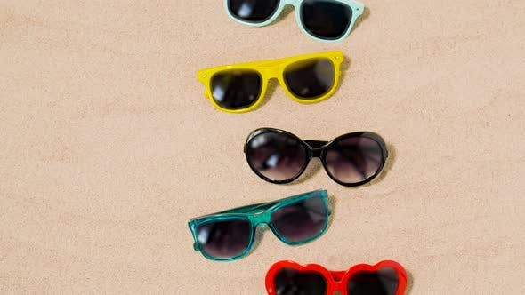 Thumbnail for Various Sunglasses on Beach Sand