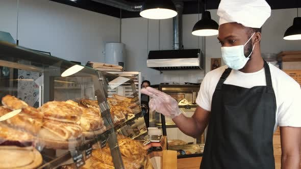 Fine African American Man in Mask Offering Pastry