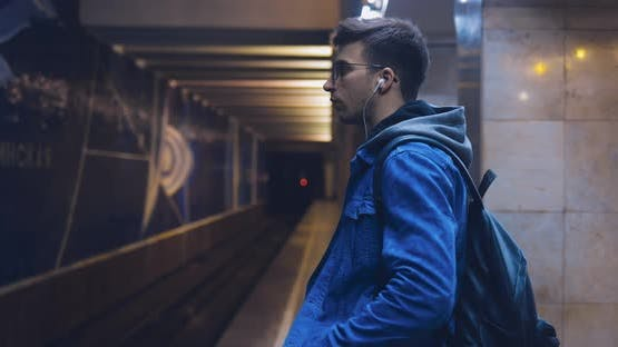 Young Man in a Jeans Jacket and Glasses is Waiting for a Train at the Metro Station