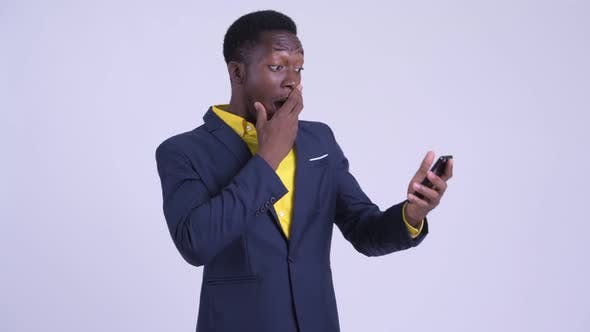 Young Happy African Businessman Using Phone and Looking Surprised