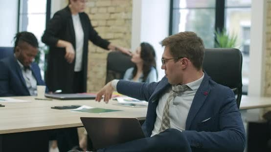 Thumbnail for Handsome Confident Caucasian Man in Eyeglasses Analyzing Startup with Blurred Colleagues Talking at