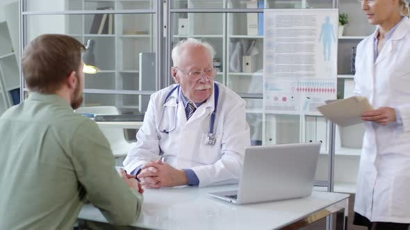 Thumbnail for Senior Doctor Working with Help of Female Assistant and Talking to Patient