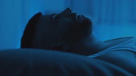 Nahaufnahme eines Soldaten, der auf dem Bett liegt und an die Decke starrt und sich mit einem Posttrauma befasst.