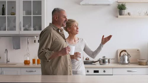Mature Couple Drinking Coffee Talking Looking Aside In Kitchen Indoor