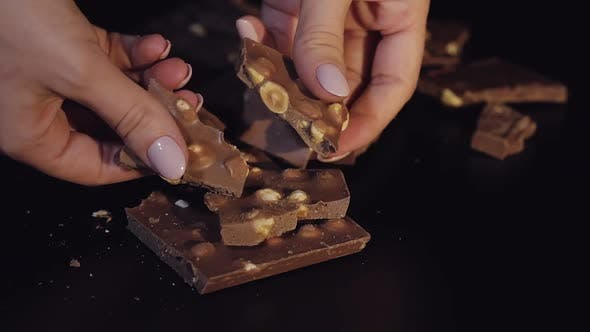 Thumbnail for Woman Breaks Black Chocolate Bar mit Nüssen