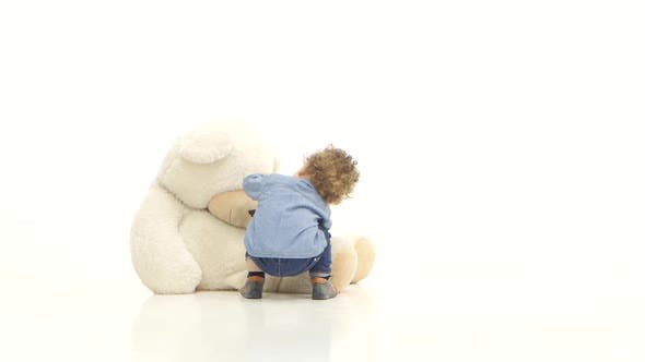 Thumbnail for Small Child Crawls on the Floor and Finds a Toy Bear. White Background