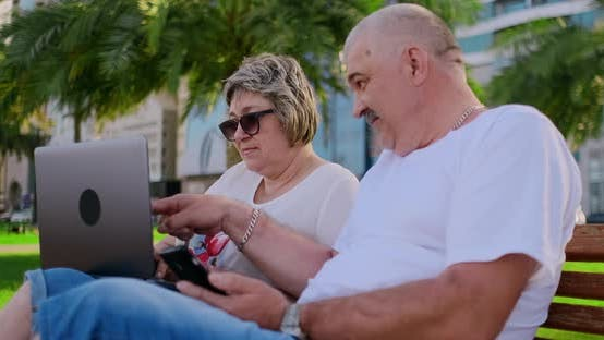Thumbnail for Happy Senior Couple Sitting on a Bench in the Summer in a Modern City with a Laptop on the