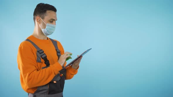 Handyman with Tablet Isolated on Blue Backgound with Copy Space Studio Shot