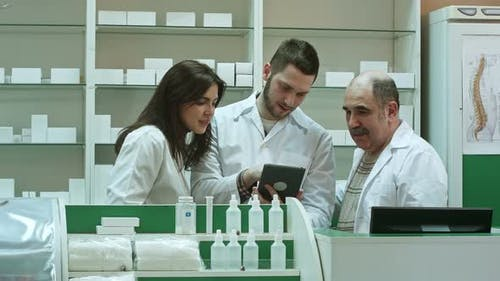 Smiling Team of Pharmacists, Two Male and One Female, Stand Side By Side in the Pharmacy Checking