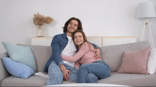 Happy Millennial Couple in Love Spending Time Together at Home Embracing on Couch and Laughing