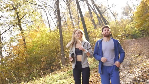 Married Couple Likes To Run Through the Autumn Forest on a Sunny Day or in the Morning Dressed in
