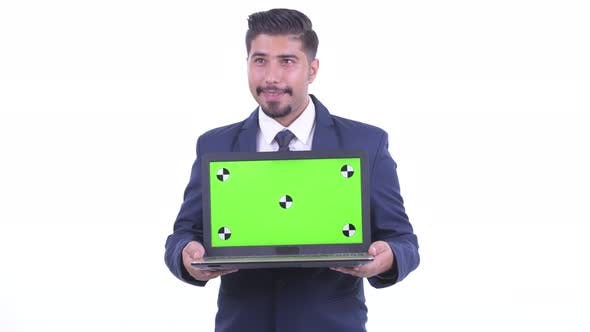 Thumbnail for Happy Bearded Persian Businessman Thinking While Showing Laptop