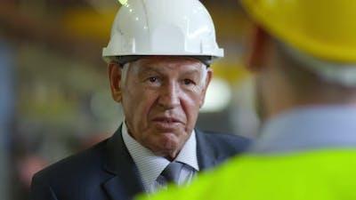 Factory boss talking to worker