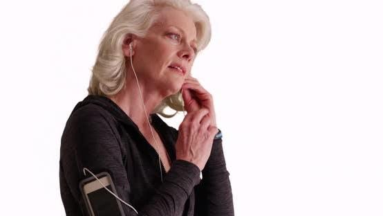 Thumbnail for Glückliche reife Frau setzen in Kopfhörer Vorbereitung für laufen auf weißem Hintergrund