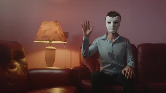 Anonymous man with mask greets with his hand while sitting on the red sofa at home