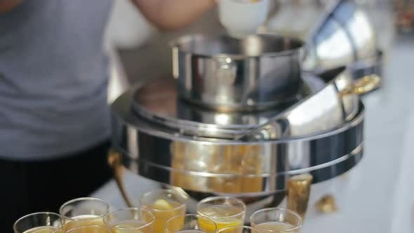 Thumbnail for Glasses Filled with Orange Juice and Alcohol and Waitress Girl Pouring Punch with Ladle Into Glasses