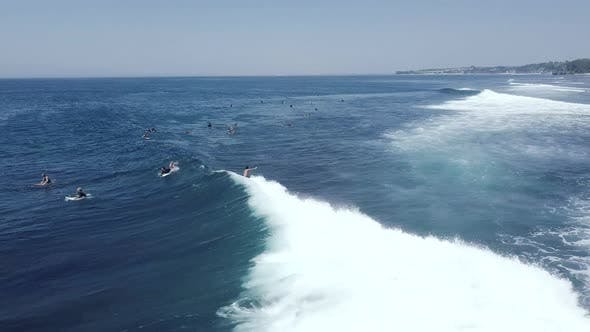 Aerial Tracking Shot of Male Surfer Riding a Big Wave Surfing in Ocean on Summer