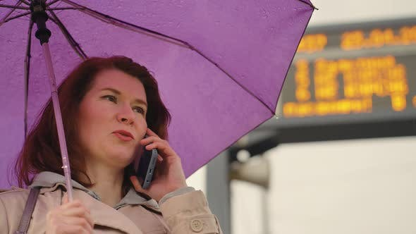 Woman with Umbrella Talking on Phone