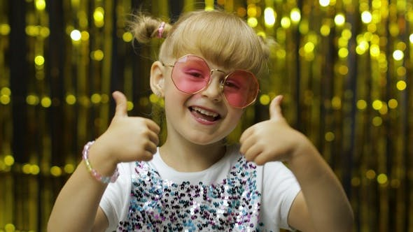 Thumbnail for Child Show Thumbs Up. Smiling, Looking at Camera. Girl Posing on Background with Foil Golden Curtain